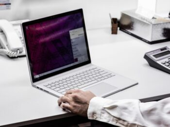 person in black blazer using macbook pro