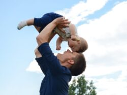 man in blue long sleeve shirt carrying baby in white onesie