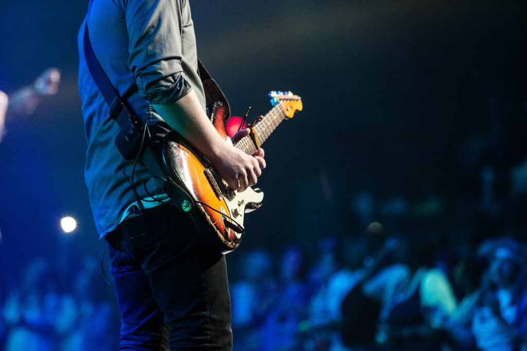 selective focus photography of man playing electric guitar on stage