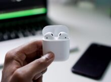 person holding wireless earbuds with charging case