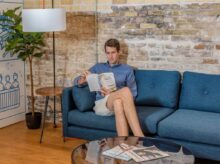 man sitting on blue sofa while reading book