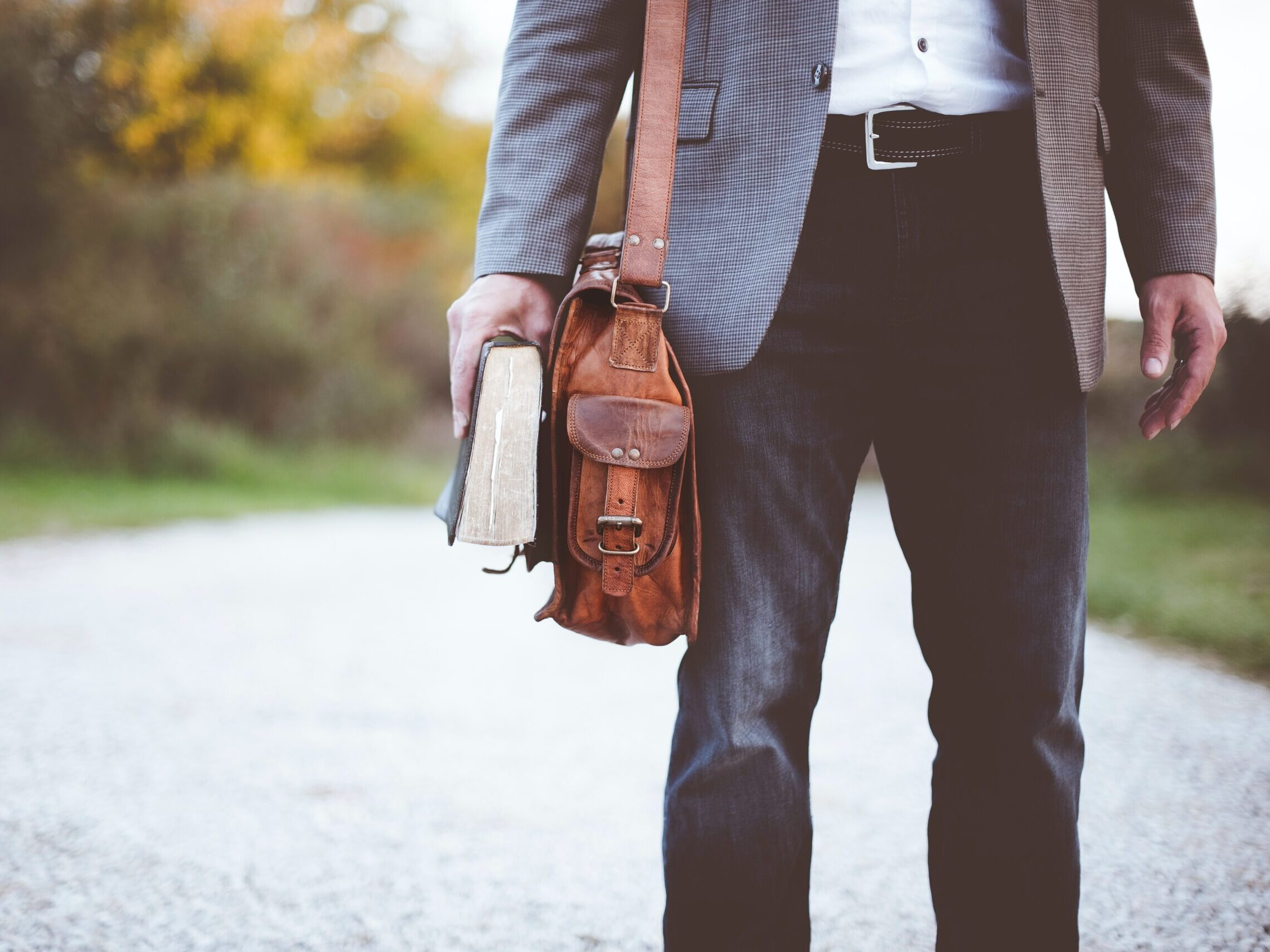 man holding book on road during daytime