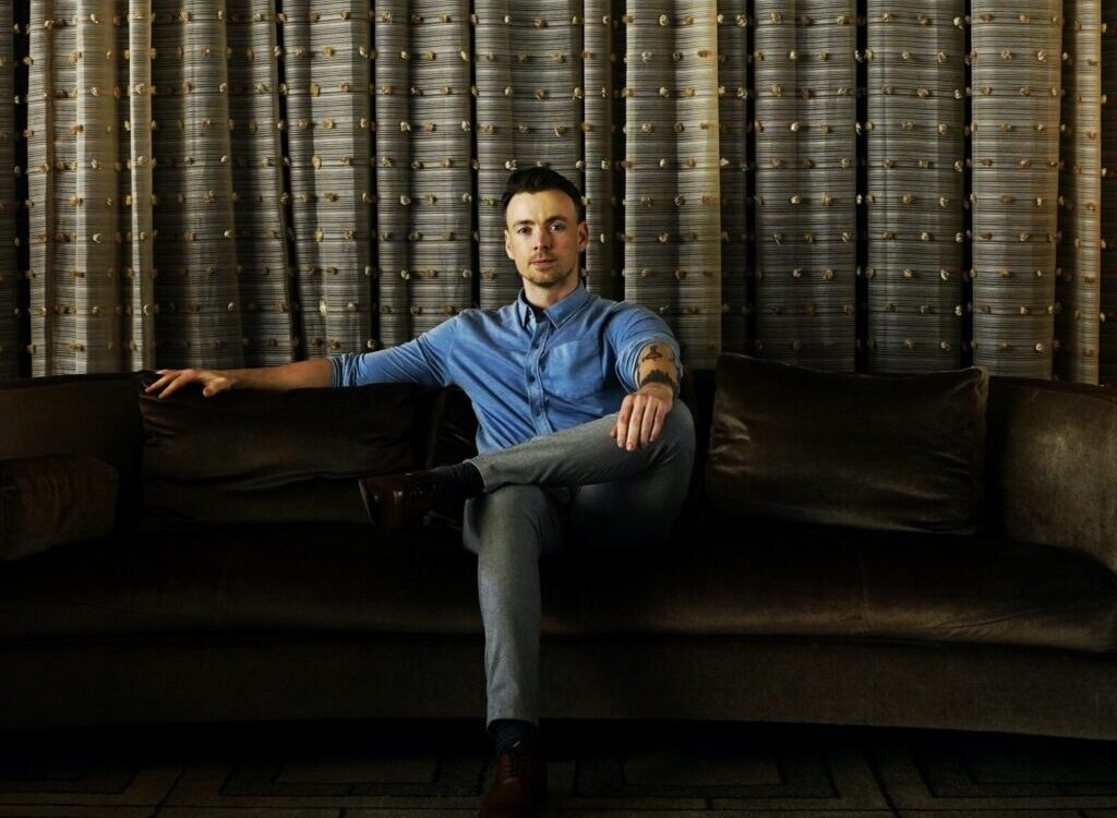man in blue shirt sitting on couch